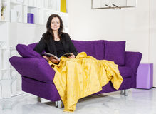 Woman on couch with magazine Stock Photos