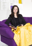 Woman on couch with magazine Royalty Free Stock Photos