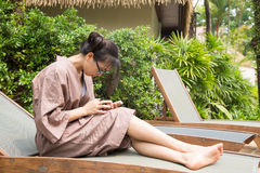 Woman couch And play smart phones. On wood bed beside the pool Stock Photo