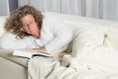 Woman on couch reading a book Stock Images