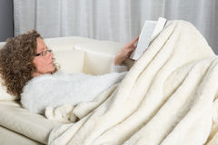Woman on couch reading a book Stock Photography