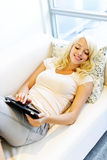 Woman on couch with tablet computer Stock Image