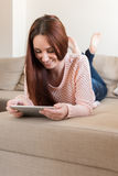 Woman on couch with tablet Royalty Free Stock Photography