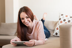 Woman on couch with tablet Royalty Free Stock Photo