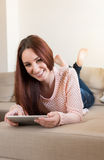Woman on couch with tablet Royalty Free Stock Images