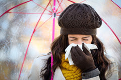 Woman coughing and blowing her nose in autumn. Woman with cold or flu coughing and blowing her nose with a tissue under autumn rain. Brunette female sneezing and Stock Images