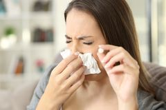 Woman coughing covering mouth with a tissue at home Royalty Free Stock Images
