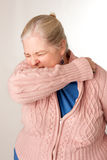 Woman Coughing/Sneezing into Elbow. An older woman coughing/sneezing into elbow in order to not spread germs Stock Photos