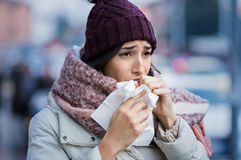 Woman coughing in winter. Young woman coughing during winter on street. Girl with cold wearing knitted cap and scarf feeling unwell. Woman feeling sick during royalty free stock images