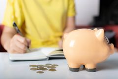 Woman count the coin in piggybank stock photo