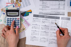 Woman counting on calculator annual home budget and thinking about his cost. stock image