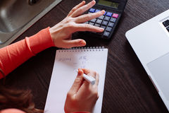 Woman counting on calculator sitting at the table. Stock Photography
