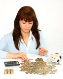 Woman counting coins. (money) using calculator isolated on a white background Royalty Free Stock Image