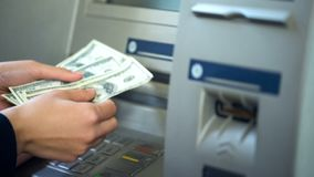 Woman counting dollars withdrawn from ATM, 24h service, easy banking operation. Stock photo stock images