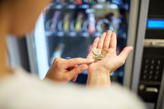 Woman counting euro coins at vending machine Royalty Free Stock Image
