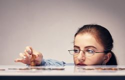 Woman counting her savings. Young attractive woman counting her savings money Royalty Free Stock Images