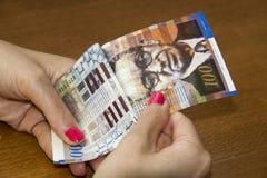 Woman counting  Israeli Sheqel banknotes. Stock Photo