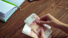 Woman counting money on the desk stock footage