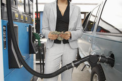 Woman Counting Money At Fuel Station Royalty Free Stock Image