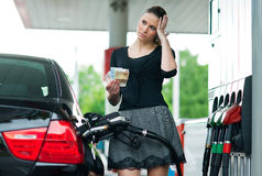 Woman counting money on gas station Royalty Free Stock Photo