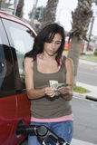 Woman Counting Money While Refueling Car Royalty Free Stock Images