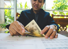 Woman is counting money with statement paper financial concept. Royalty Free Stock Images
