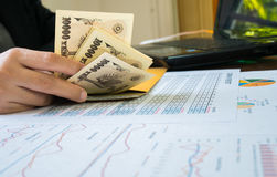 Woman is counting money with statement paper financial concept. Royalty Free Stock Photo