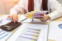 Woman counting money and use calculator, Euro banknotes. Business or stock market concept image Royalty Free Stock Image