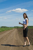 Woman on a country road. Girl hitching a ride on a country road Stock Photo