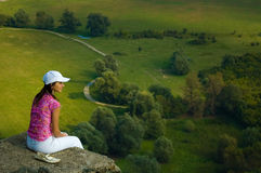 Woman in countryside. Woman sat on cliff edge looking over green countryside landscape stock photos