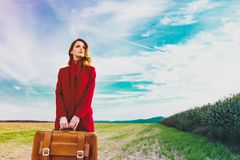 Woman at countryside with suitcase. Portrait of young woman in red coar at autumn countryside with suitcase stock photos