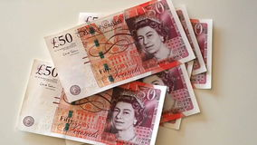 Woman counts for 50 pound banknotes. Detail of hands of a woman counting 50 pound banknotes on a white table. Print or coin of 2016, Bank of England. The pound stock video