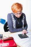 Woman counts taxes Stock Photo