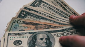 Woman countslot of small dollar bills on the table with a white background macro close up stock footage