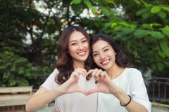 Woman couple having fun outdoors and making heart symbol Royalty Free Stock Image
