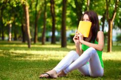 Woman cover the face with book at park Stock Image