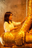 Woman is cover with gold leaves buddha. Royalty Free Stock Image