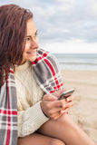 Woman covered in blanket with cellphone at beach Stock Images