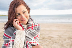 Woman covered with blanket using cellphone at beach Stock Images