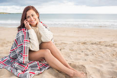 Woman covered with blanket using cellphone at beach Stock Photos