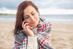 Woman covered with blanket using cellphone at beach Royalty Free Stock Image