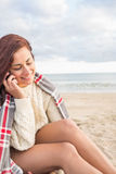 Woman covered with blanket using cellphone at beach Royalty Free Stock Photography