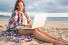 Woman covered with blanket using laptop at beach Stock Photography