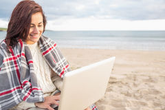 Woman covered with blanket using laptop at beach Royalty Free Stock Photo