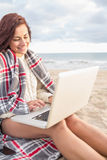 Woman covered with blanket using laptop at beach Royalty Free Stock Image