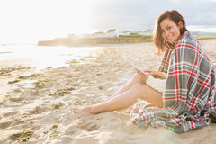 Woman covered with blanket using tablet PC at beach Stock Photos