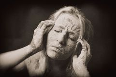Woman covered in dry cracked clay mask holding her head royalty free stock image