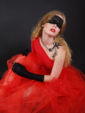 Woman with covered eyes in red dress royalty free stock photography