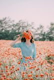 Woman covered her face with bouquet of poppies. Young woman wearing in blue dress standing in flowers meadow and covered her face with bouquet of red poppies in stock image