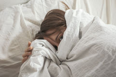 Woman covered her face with pillow. Looking at camera. Royalty Free Stock Photos